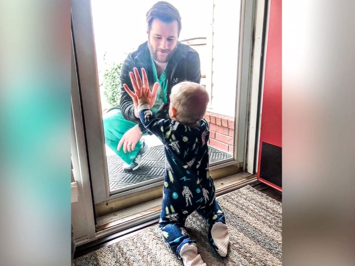 Doctor sees son crawl for first time through glass door after coronavirus separates family