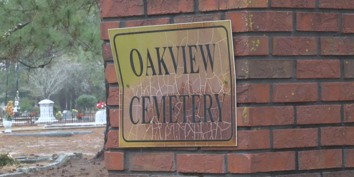 Fence separating graves in Camilla comes down