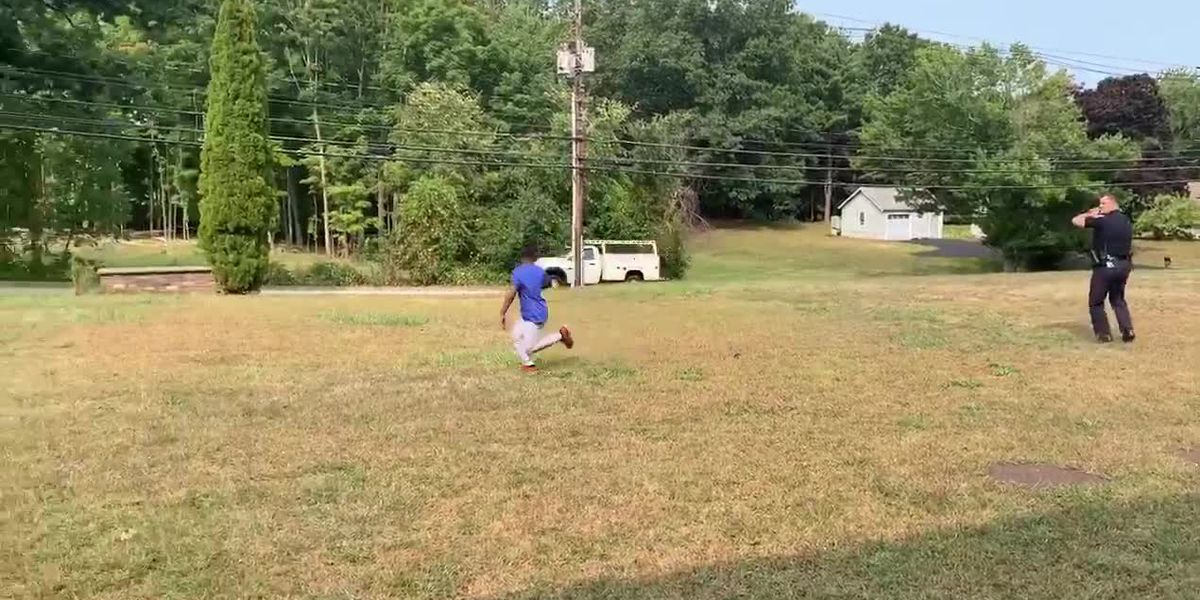 Officer stops to toss the football with boy playing catch by himself