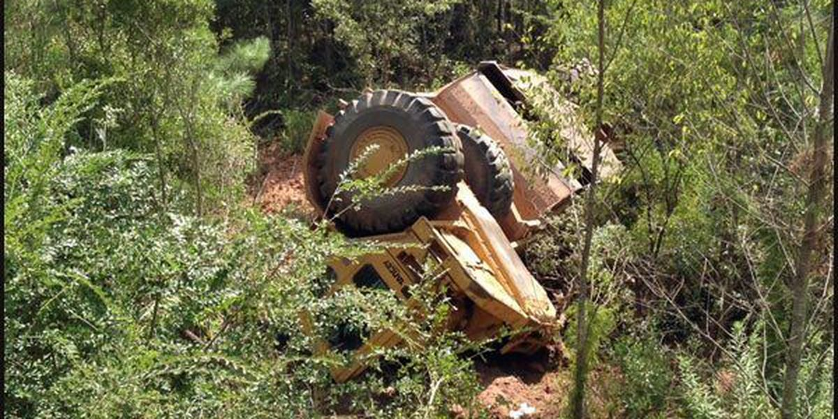 Man injured after construction vehicle flips down landfill hill